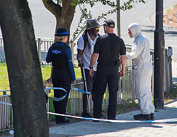 © Licensed to London News Pictures.  25/06/2018; Bristol, UK. Police talk to a member of the public near the scene of murder with police and forensics. A murder investigation has been launched after man dies and two are seriously injured in an armed burglary in Prewett Street, Redcliffe, in the early hours of the morning. It is reported that neighbours have told of hearing bloodcurdling screams of as three men were attacked with a sword-like knife. Two other men who suffered life-threatening injuries have been taken to hospital. It is reported that two men from London have been arrested in connection with the incident. Photo credit: Simon Chapman/LNP