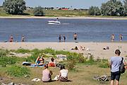 Nederland, nijmegen, 5-8-2020 Vooral jonge mensen zoeken verkoeling aan de oevers van de waal op deze tropisch warme zomerdag . Het is eigenlijk verboden in de rivier te zwemmen vanwege de stroming en het drukke scheepvaartverkeer . Deze strandjes  liggen tussen de kribben in de Stadswaard . Een plezierjacht,kruiser, komt juist voorbij . De Waal is voor de pleziervaart een gevaarlijke rivier .Foto: ANP/ Hollandse Hoogte/ Flip Franssen