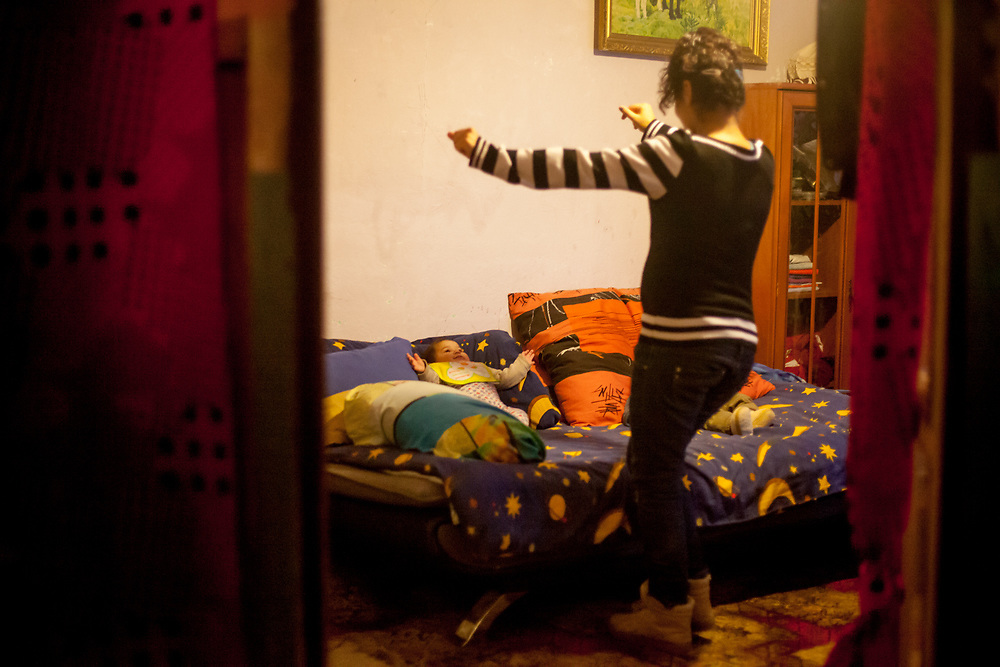 """Milena's daughter is dancing for her 4 months old son in the new compensatory flat the family moved in after their long term residence at """"Hrebenova 34-36"""" which was demolished by the city of Kosice in August 2014. After a longer period of time with different flats the family found their final destination in another building at the Lunik IX housing estate. Lunik IX has officially 6542 registered (12/2015) inhabitants, almost all of them are of Roma ethnicity and about 2,563 inhabitants are children and teenagers."""