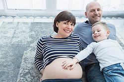 Portrait of parents lying on carpet with son touching mother's belly