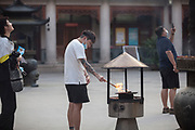 A man  burning incense in the Jing'an Temple courtyard , Shanghai, China