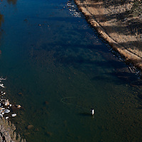 A fly fisherman makes a cast while fishing the Crooked River in Oregon during winter.
