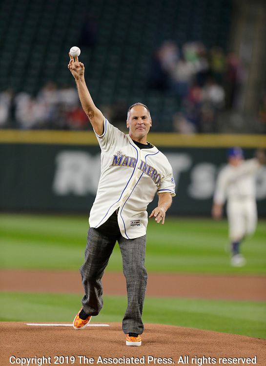 Retired MLB player Omar Vizquel throws the ceremonial first pitch before a baseball game between the Seattle Mariners and the Chicago White Sox, Sunday, Sept. 15, 2019, in Seattle. (AP Photo/John Froschauer)