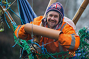 Dan Hooper, widely known as Swampy during the 1990s, smiles as he holds a lock-on arm tube in a basket suspended from a bamboo tripod positioned in the river Colne on 8th December 2020 in Denham, United Kingdom. The climate and roads activist had occupied the tripod the previous day in order to delay the building of a bridge as part of works for the controversial HS2 high-speed rail link and a large security operation involving officers from at least three police forces, the National Eviction Team and HS2 security guards was put in place to facilitate his removal.
