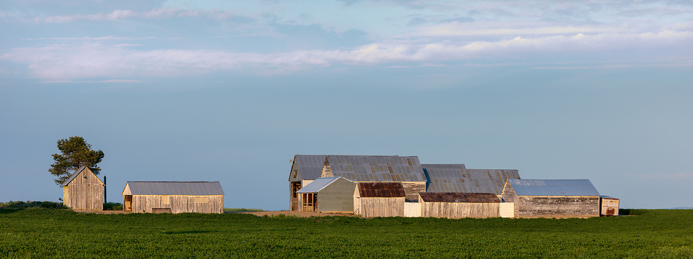 Editions of 17<br /> Evening light on the geometric shapes of farm buildings on the Camas Prairie in Idaho