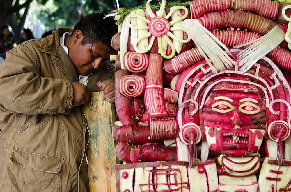 Young man carving a mask of Mictlantecuhtli, the Mixtec God of Death, at Noche de Rabanos / Night of the Radishes festival, Oaxaca, Mexico.