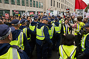 A large group of Metropolitan Police officers moves towards thousands of students attending the National Demonstration for a Free Education on 4th November 2015 in London, United Kingdom. The demonstration was organised by the National Campaign Against Fees and Cuts NCAFC in protest against tuition fees and the Government's plans to axe maintenance grants from 2016.