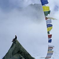 Great Sail Peak Expedition, Baffin Island, Canada. Alex Lowe (MR) on boulder beside Tibetan prayers flags in base camp.