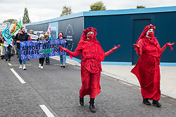 Members of the Red Rebel Brigade join fellow climate activists from Extinction Rebellion at a protest against the expansion of Stansted Airport on 29 August 2020 in Bishop's Stortford, United Kingdom. The activists are calling on Manchester Airports Group to withdraw their appeal, for which planning permission was previously refused by Uttlesford District Council, to be able to expand Stansted Airport from a maximum of 35 million to 43 million passengers a year, as well as calling on the Government to halt all airport expansion in order to maintain its commitments under the Paris Agreement.