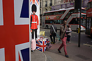 With a London Routemaster bus in the background, a successful young black man walks past the image of a Coldstream guardsman and Union Jack flag that appear on a poster outside a tourist shop in central London. Located on a street corner near the British Museum in central London, we see these iconic symbols for Britishness, for the tourism industry and for Britian's Uk identity.