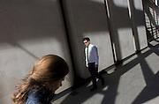 Man walks past woman in narrow sunlight street in the City of London.