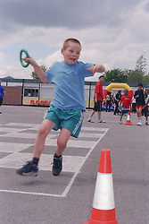 Primary school boy taking part in relay race during P,E, lesson,