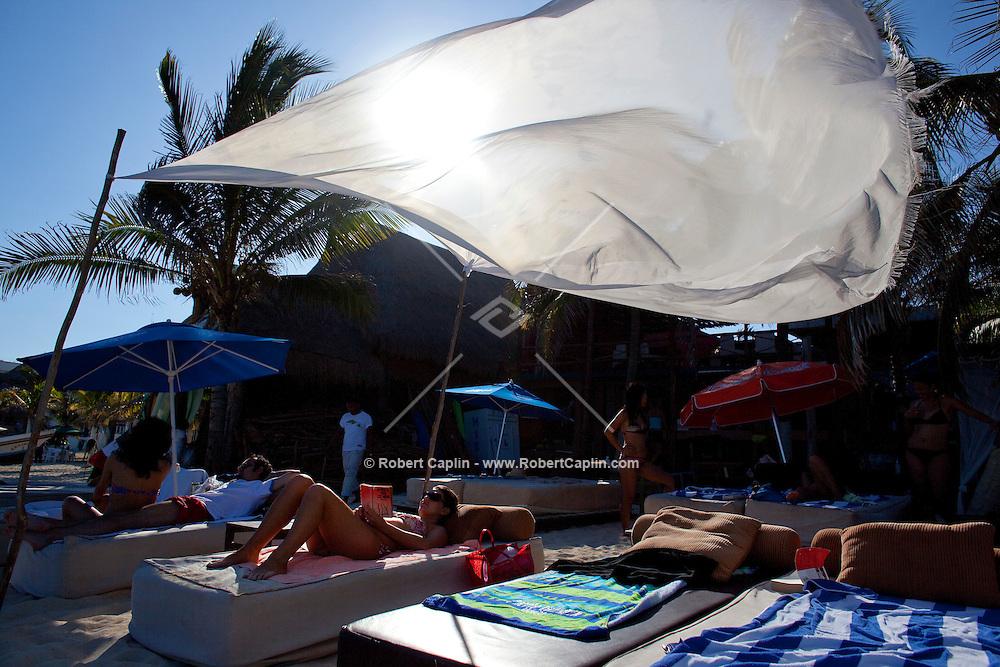 Sunbathers enjoy the beach in Playa Del Carmen, Mexico. (Photo By Robert Caplin)