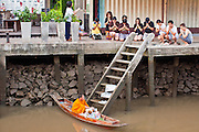"10 JULY 2011 - AMPHAWA, SAMUT SONGKRAM, THAILAND:   A Buddhist monk from Wat Amphawan Chetiyaram in Amphawa, Thailand, about 90 minutes south of Bangkok, collects alms from people ""making merit"" on the main canal during his alms round. Most of the monks from the temple use boats to go from house to house on their alms rounds. The Thai countryside south of Bangkok is crisscrossed with canals, some large enough to accommodate small commercial boats and small barges, some barely large enough for a small canoe. People who live near the canals use them for everything from domestic water to transportation and fishing. Some, like the canals in Amphawa and nearby Damnoensaduak (also spelled Damnoen Saduak) are also relatively famous for their ""floating markets"" where vendors set up their canoes and boats as floating shops.      PHOTO BY JACK KURTZ"