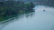 Single boat creating ripples in the Perfume River or Huong River. It is around 80 kilometers long, and owes its name to the fact that it flows through many forests of aromatic plants before reaching Hue.