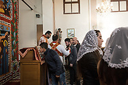 Istanbul, Turkey. A Syrian Christian in the congregation of the Samatya Kilisesi takes communion offered by the Syriac bishop in the diverse church in Istanbul's historic Fatih neighbourhood.