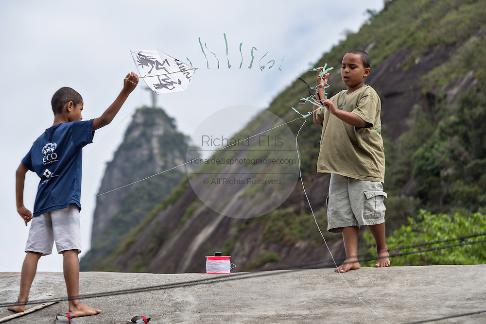 Young Brazilian boys fly a kite in the Favela Santa Marta with the Christ Redeemer statue behind in Rio de Janeiro, Brazil.