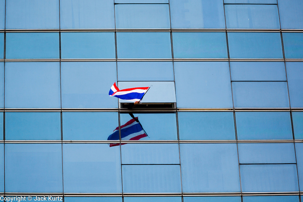 21 JANUARY 2014 - BANGKOK, THAILAND: A supporters of Suthep Thaugsuban waves a Thai flag from the window of an office building on Thanon Naradhiwas Rajanagarindra in the financial district of Bangkok. Suthep, the leader of the anti-government protests and the People's Democratic Reform Committee (PDRC), the umbrella organization of the protests, led a march through the financial district of Bangkok Tuesday. Shutdown Bangkok has entered its second week with no resolution in sight. Suthep is still demanding the caretaker government of Prime Minister Yingluck Shinawatra resign and the PM says she won't resign and intends to go ahead with the election.     PHOTO BY JACK KURTZ