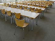 Rows of empty chairs and tables indoors