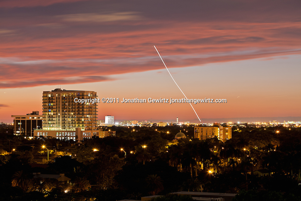 An aircraft takes off from Miami International Airport at dusk. WATERMARKS WILL NOT APPEAR ON PRINTS OR LICENSED IMAGES.