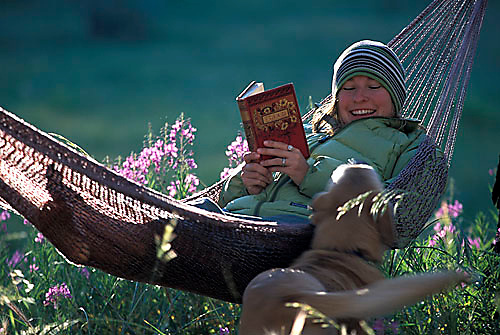 Sarah Meredith relaxing in hammock reading a book in South Lake Tahoe, CA.<br />