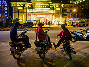 """13 FEBRUARY 2019 - SIHANOUKVILLE, CAMBODIA:  Cambodian motorcycle taxi drivers wait for fares across the street from the New MGM Casino, a Chinese owned casino in Sihanoukville. There are about 80 Chinese casinos and resort hotels open in Sihanoukville and dozens more under construction. The casinos are changing the city, once a sleepy port on Southeast Asia's """"backpacker trail"""" into a booming city. The change is coming with a cost though. Many Cambodian residents of Sihanoukville  have lost their homes to make way for the casinos and the jobs are going to Chinese workers, brought in to build casinos and work in the casinos.      PHOTO BY JACK KURTZ"""