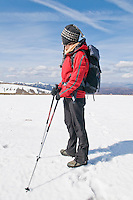 Female hiker in red jacket takes in view of Cairngorm mountains from near summit of Cairn Lochan, Scotland