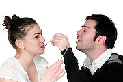 man feeds cream cake to a woman