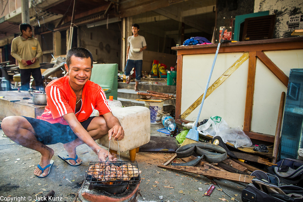"""11 DECEMBER 2012 - BANGKOK, THAILAND:  A worker grills chicken in front of the empty building he lives in while he works on its demolition at """"Washington Square"""" a notorious entertainment district off Sukhumvit Soi 22 in Bangkok. Demolition workers on many projects in Thailand live on their job site tearing down the building and recycling what can recycled as they do so until the site is no longer inhabitable. They sleep on the floors in the buildings or sometimes in tents, cooking on gas or charcoal stoves working from morning till dark. Sometimes families live and work together, other times just men. Washington Square was one of Bangkok's oldest red light districts. It was closed early 2012 and is being torn down to make way for redevelopment.   PHOTO BY JACK KURTZ"""