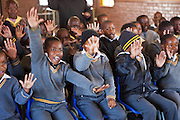 Children from Matsie Steyn primary school, Sharpeville, Vereeniging, South Africa, watch and participate in an interactive performance of the 'No Monkey Business' puppet show, an AREPP: Theatre for Life production providing interactive social life skills education to school children through theatre productions. They are based in Johannesburg, South Africa and are on tour for 3 months doing performances everyday at schools across the country.