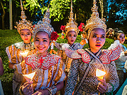 12 AUGUST 2016 - BANGKOK, THAILAND: Thai students in traditional Thai costumes participate in the a candlelight vigil to honor Queen Sirikit of Thailand. Thais celebrated the Queen's birthday Friday. Queen Sirikit of Thailand, was born Mom Rajawongse Sirikit Kitiyakara on 12 August 1932. She married  Bhumibol Adulyadej, King of Thailand (Rama IX) in 1950. He is the longest serving monarch in the world and she is longest serving consort of a monarch. Her birthday, like the King's Birthday (which falls on Dec. 5),  is a national holiday in Thailand. Her birthday, August 12, is also celebrated as Mother's Day in Thailand.      PHOTO BY JACK KURTZ