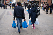 People carrying plastic carrier bags of shopping on 14th March 2020 in Birmingham, United Kingdom. In recent years following global concerns over plastics use and in particular the carrier bag, there has been a greatly reduced number of bags being used, although street markets, who use blue carrier bags like this seem yet to promote more environmentally friendly options or to ban plastic bag use altogether.
