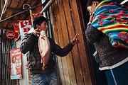 Un joven sostiene un pescado que ofrece para su venta en las calles de Rinconada.