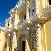 Front facade of the distinctive  and ornate yellow and white exterior of the Iglesia y Convento de Nuestra Senora de la Merced in downtown Antigua, Guatemala.