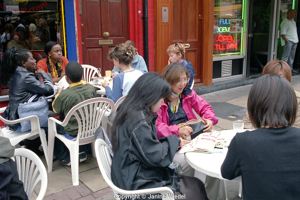 Multicultural group eating on the street in Brick Lane East End London