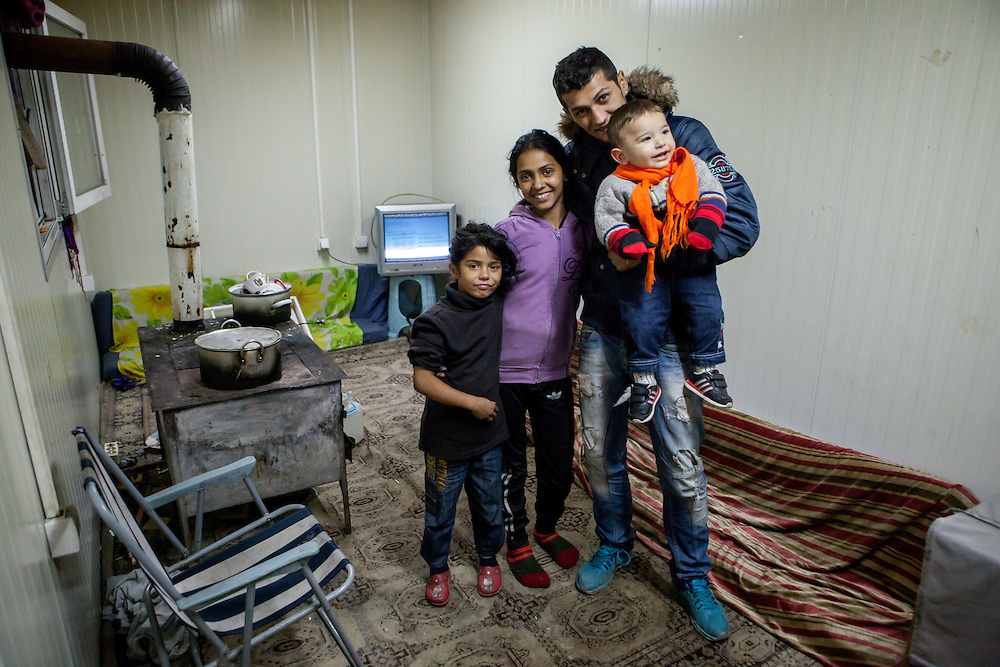 Inside in one of the new housing facilities in Konik Camp located in the suburbs of the city of Podgorica, Montenegro. A huge fire in 2012 detroyed a big part of the refugee camp and many of the inhabitants are living now in containers. Pictured members of the Banushi family Robert Banushi holding the child, Zadji Banushi (younger girl) and Elizabeta Banushi.