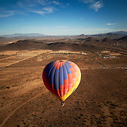 A hot air balloon floats above the desert in North Phoenix, Arizona. The balloon from Hot Air Expeditions in Phoenix, Arizona leaves for dawn and dusk rides and concludes with a champagne toast.