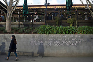 """A woman in Melbourne's Central Business District walks past a message written in chalk that encourages passersby to """"choose vegan."""""""