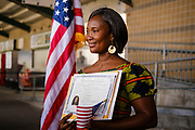 17 SEPTEMBER 2020 - DES MOINES, IOWA: NUNEE SIAH TARLEY holds her naturalization certificate as she poses for pictures next to the American flag after a naturalization ceremony at Principal Park, a minor league baseball stadium in downtown Des Moines. About 75 people from 32 countries were naturalized as US citizens Thursday. It was the last citizenship ceremony in Des Moines before citizenship fees dramatically increase. Starting Oct. 2, the fee to apply for U.S. citizenship will increase from $640 to $1,160 if filed online, or $ 1,170 in paper filing, a more than 80% increase in cost. Advocates for immigration are afraid the new fees will be too expensive for many immigrants and say it's an effort by the Trump Administration to limit the number of new citizens welcomed into the United States. Because of the COVID-19 pandemic, there has been dramatic slow down in the number of naturalization ceremonies this year.          PHOTO BY JACK KURTZ