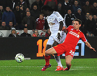 Swansea City's Bafetibis Gomis is tackled by Liverpool's Joe Allen<br /> <br /> Photographer Kevin Barnes/CameraSport<br /> <br /> Football - Barclays Premiership - Swansea City v Liverpool - Monday 16th March - The Liberty Stadium - Swansea<br /> <br /> © CameraSport - 43 Linden Ave. Countesthorpe. Leicester. England. LE8 5PG - Tel: +44 (0) 116 277 4147 - admin@camerasport.com - www.camerasport.com
