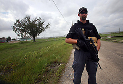 03 Sept 2008. New Orleans, Louisiana. Lower 9th Ward..After hurricane Gustav. Jake Spahr, private security contractor with Oakley Services International (OSI) patrols Brad Pitt's 'Make It Right' Foundation houses in the Lower 9th ward. Spahr also extends his foot patrols to take in other neighbourhood homes and a school that he protects against looting. Spahr, armed with a Beretta Storm rifle and protected with body armor is veteran of many foreign conflicts. He checks doors and windows on the Brad Pitt Homes..Photo; Charlie Varley.