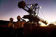 Workers watch an ore reclaimer at work on site in the Pilbara