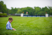 Sights from the 2013 Queens Cup Steeplechase - April 27, 2013: A young boy sits on the race course during opening ceremonies