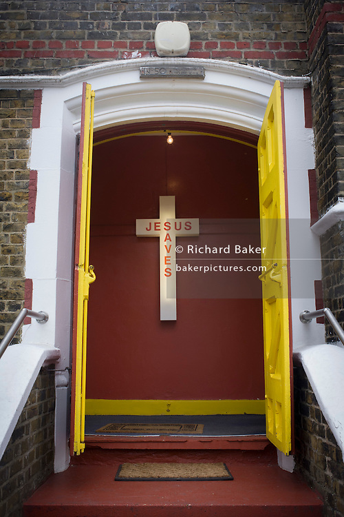 A Jesus Saves neon sign in the entrance of an evangelical church in Peckham, south London. The yellow doors at the top of steps with two doormats are open to welcome worshippers of this Christian community in south London. Inside are the voices and cries of the faithful, gathered on Easter Sunday, an important date in the Christian calendar. The cross is mounted on the inside wall, illuminated by its neon tube inside the plastic outer casing.