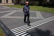 A man with a camera and wearing a striped shirt steps along a walkway of matching parallel lines and stripes, outside the Musee Farbre on Boulevard de Bonne Nouvelle on 19th June 2016, in Montpellier, France.
