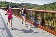 Rosendale, New York - Rebecca Zucconi, left, and Sarah LeMoy cross the railroad trestle during the Shawangunk Ridge Trail Run/Hike 20-mile race on Sept. 20, 2014.