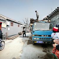 China,Beijing ,13 maart 2008..Chinese bewoners en werklieden in een gerenoveerde Huton (oud buurtje) in de oude stadswijk van Beijing..Dit is 1 van de weinig overgebleven Hutons van Beijing. De meeste oude wijkjes zijn met de grond gelijk gemaakt en hebben plaats gemaakt voor grote hogenieuwe kantoorgebouwen en flats..Met het vooruitzicht op de Olympische Spelen in augustus van dit jaar zijn enkele overgebleven Hutons gerenoveerd speciaal voor de toeristen.