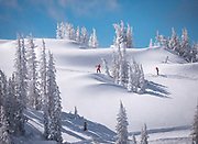 A pair of skiers traverses the top of the hill to reach the steeps of Curecanti at Monarch Mountain, as the last flakes of an epic powder morning soften the March sunshine.