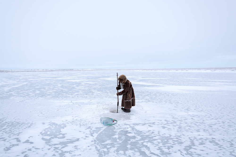 Lena, a Nenets woman, breaks open the ice to collect water for drinking and washing.
