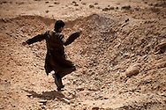 A rebel leaps into the a crator in a massive Ammo dump outside of Abjabiya on March 1, 2011. Qadaffi's airforce has dropped many bombs around the storage area.